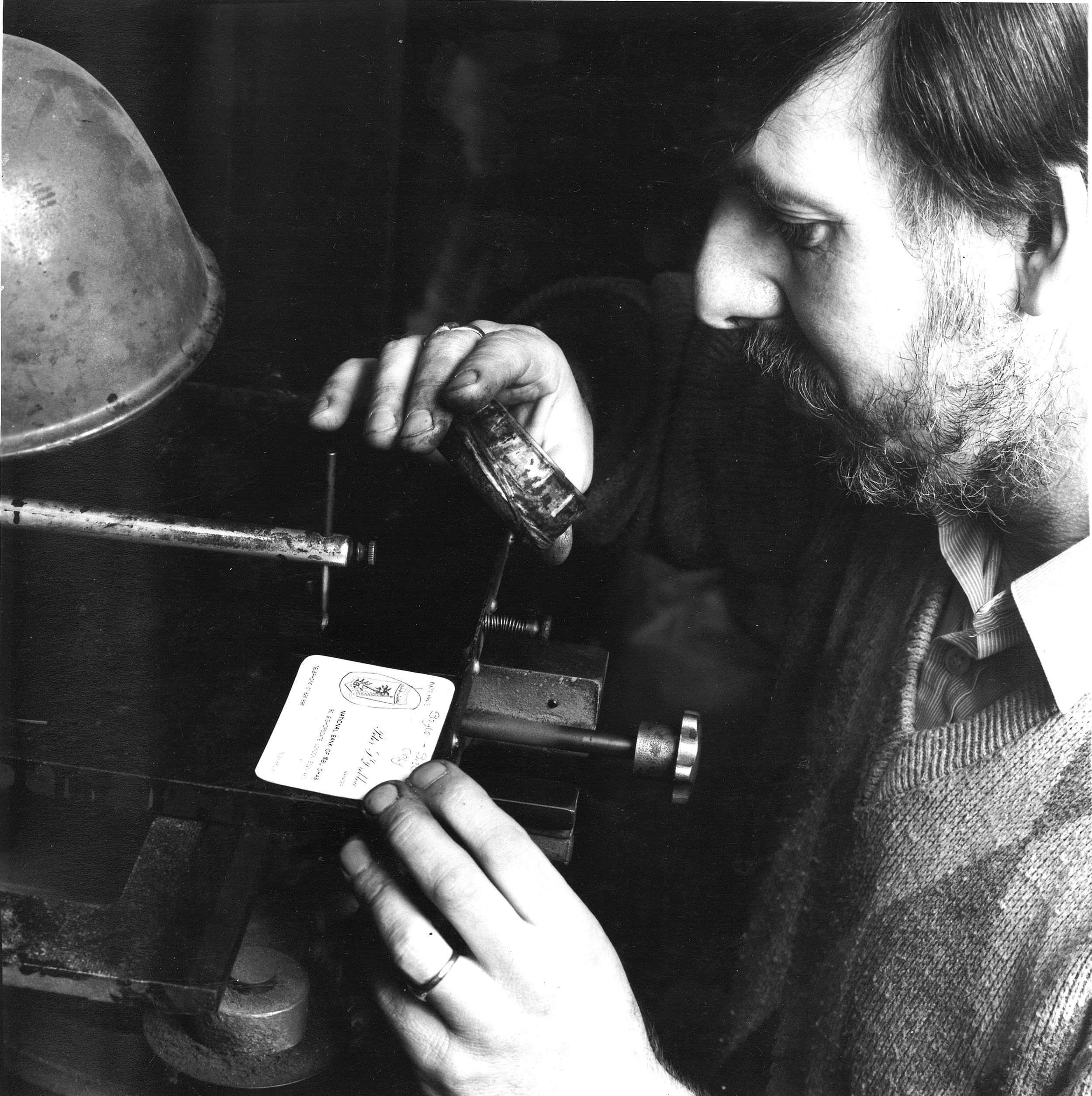 Man looking at printed card through magnifying glass