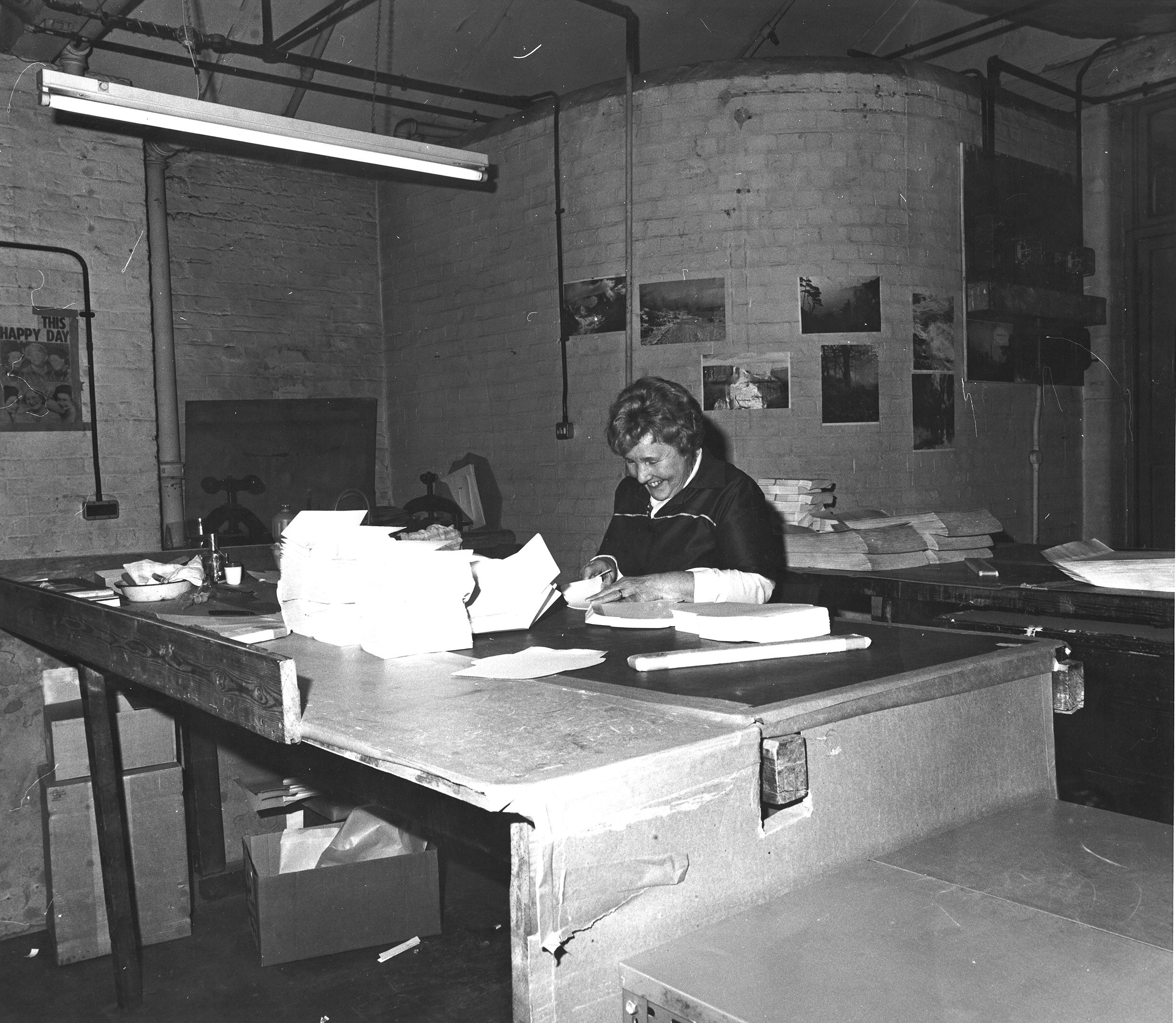 Woman making envelopes at desk