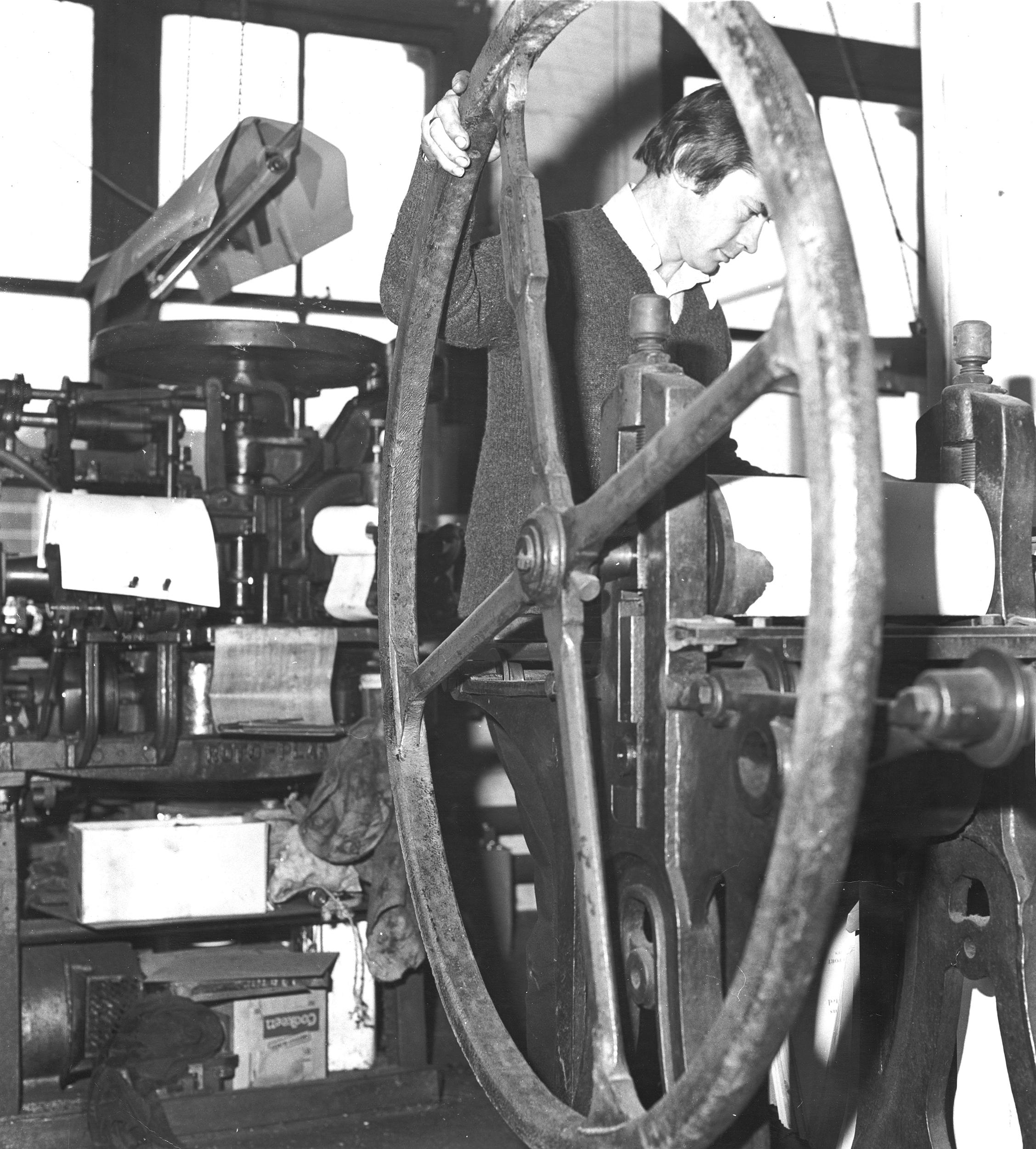 Man operating printing press