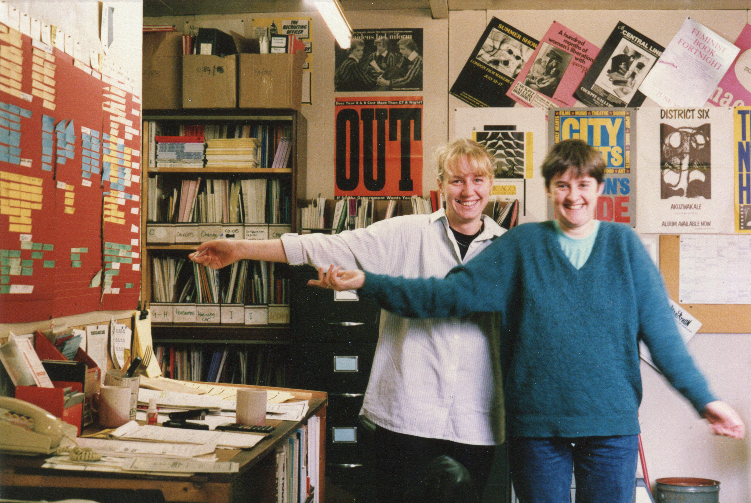 Two women standing in front of wall with posters