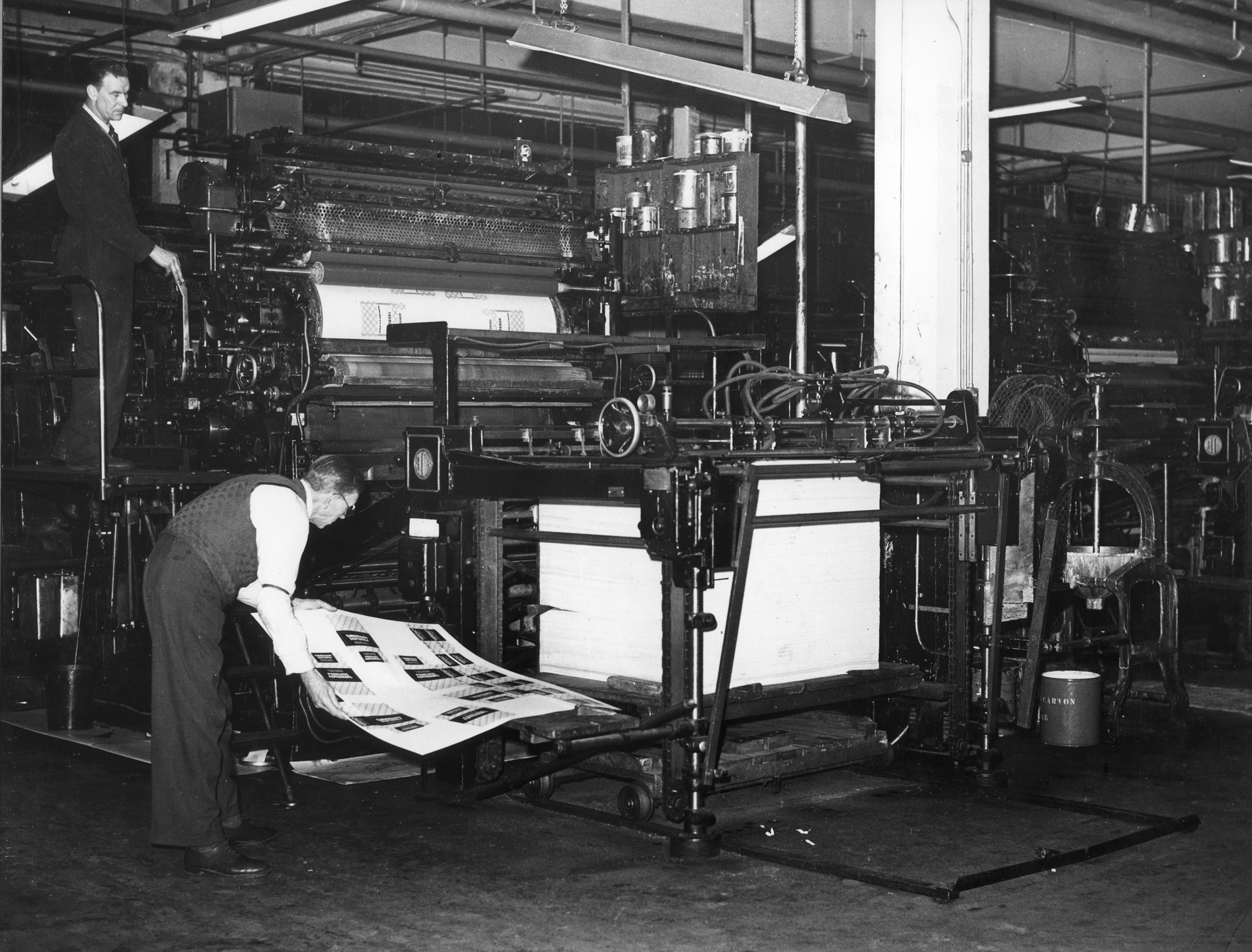 Two men at work on printing machine