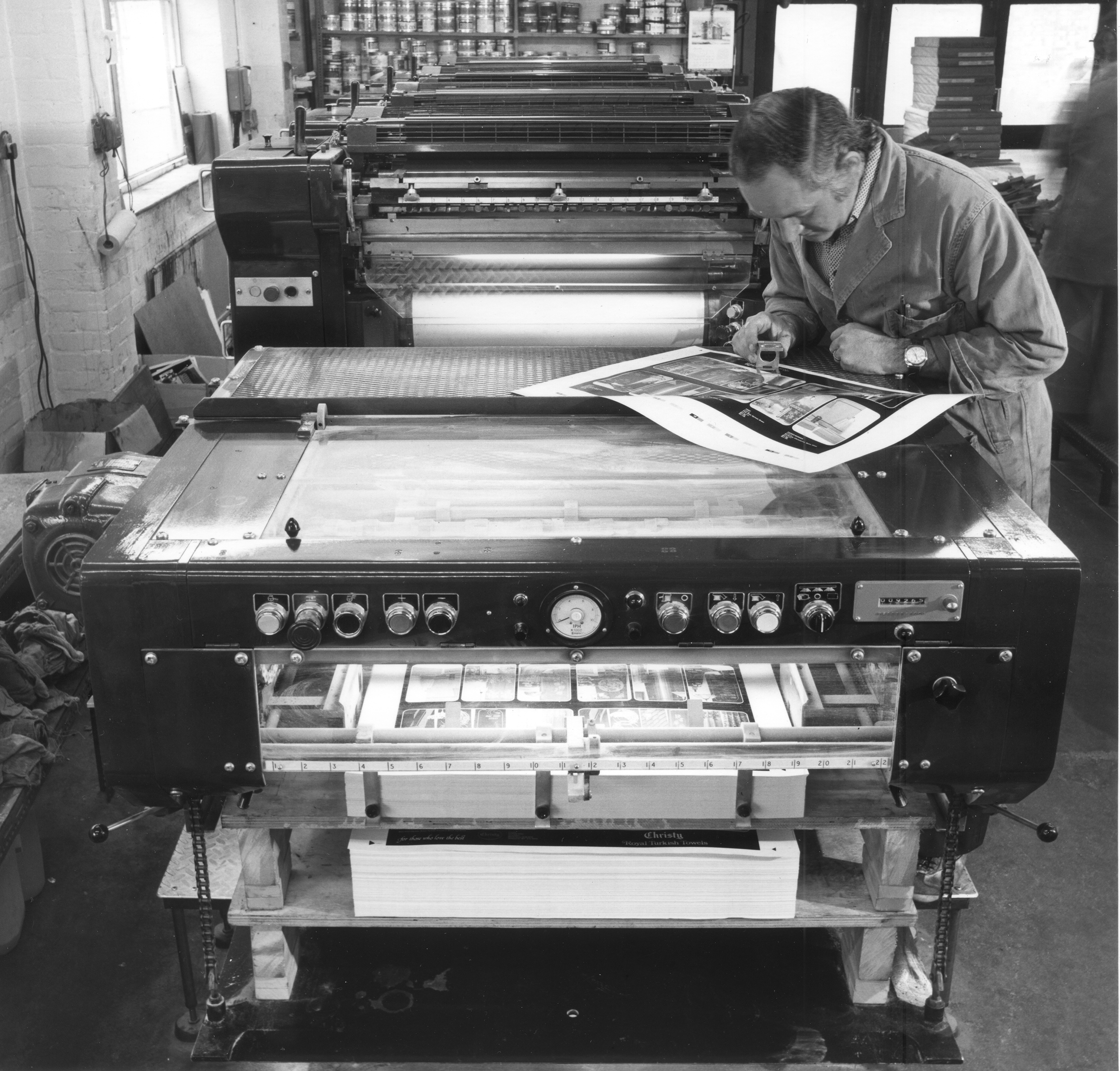 Man at printing press looking at print