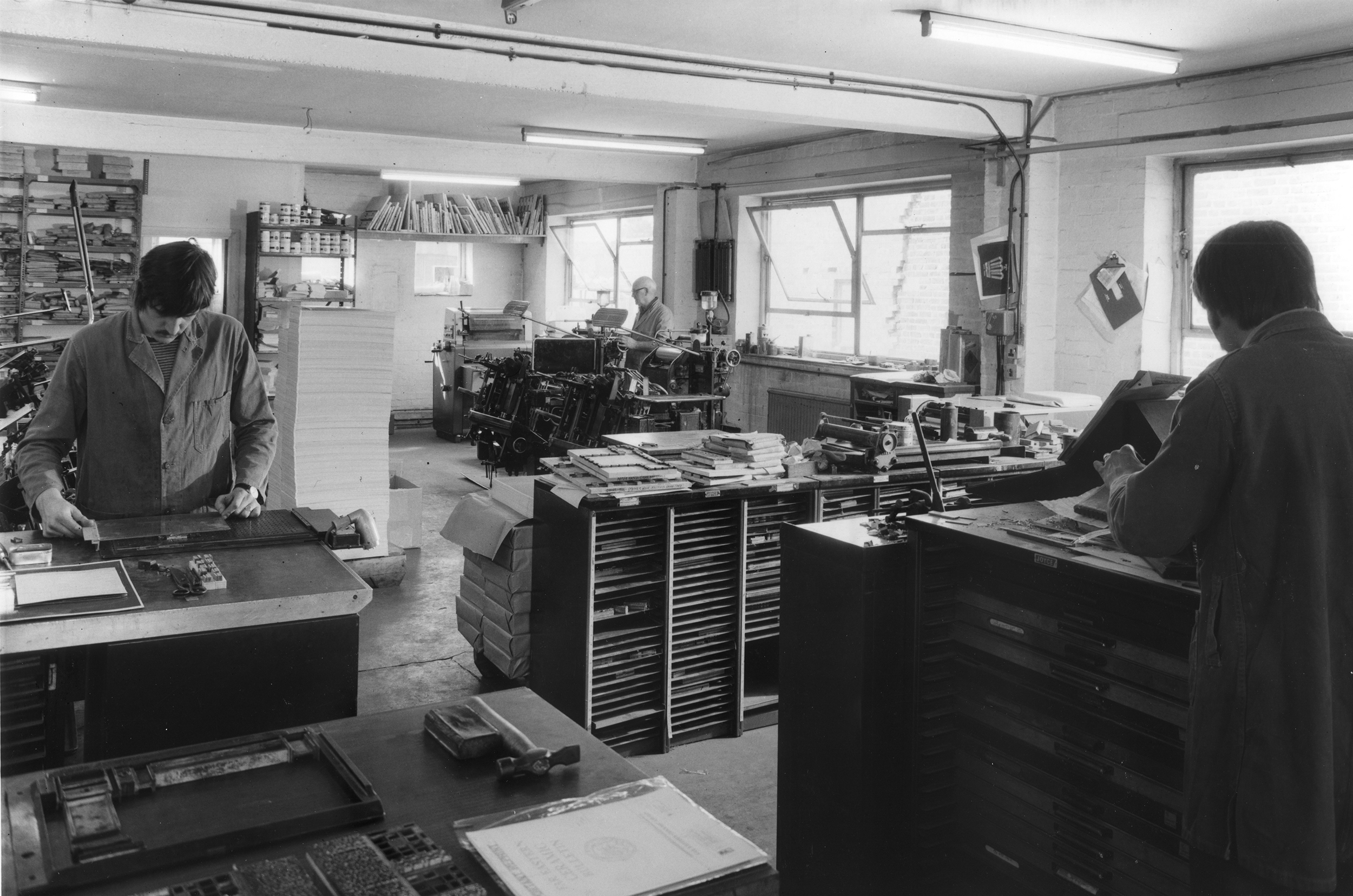 Three men at work in printing workshop