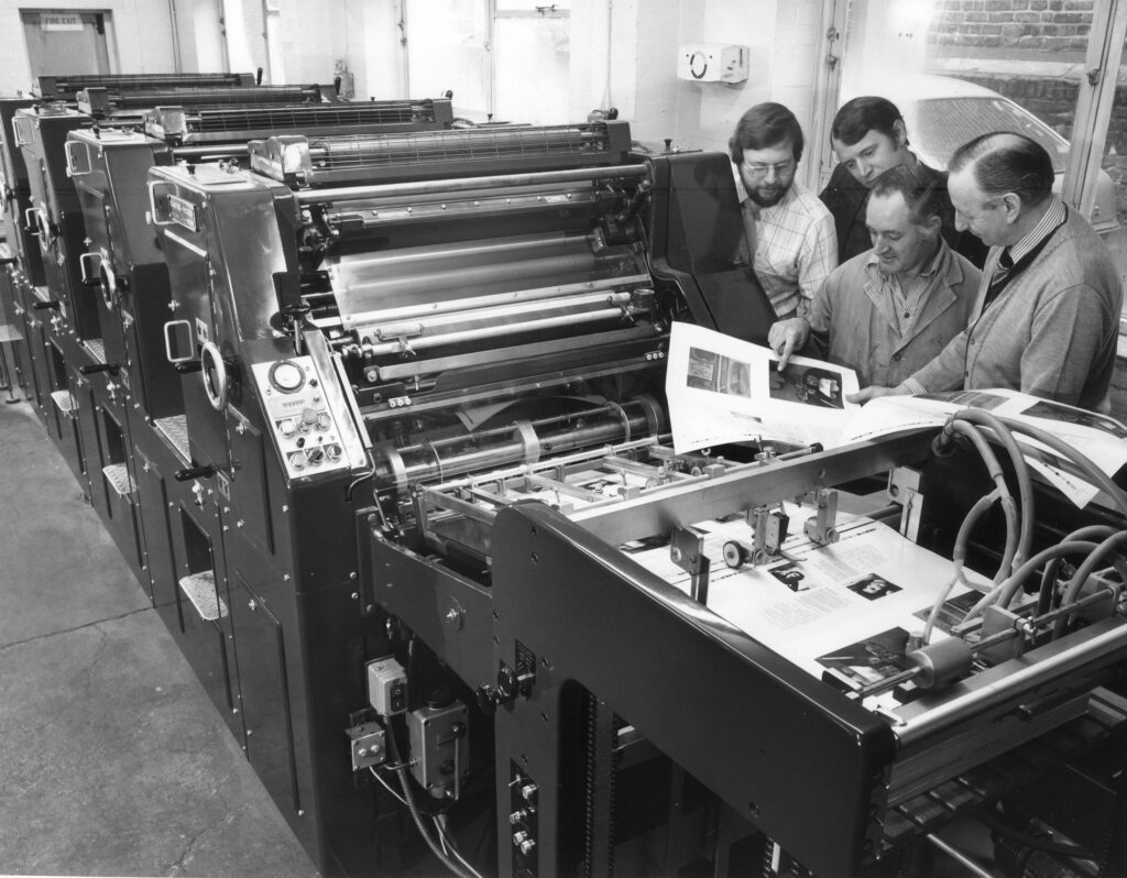 Four men looking at printed sheet by a printing press