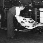 Black and white photo of man examining printing press